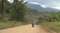 woman walking down a lonely dirt road in africa video