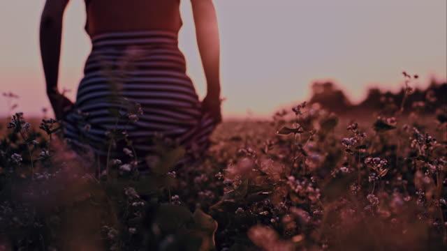 SLO MO Woman walking in field of buckwheat video