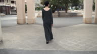 Woman walking in the city rear back view video