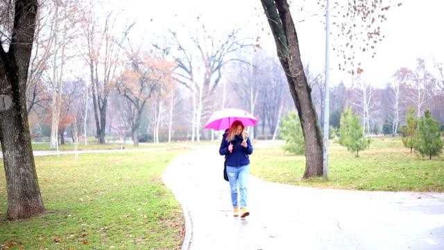 Woman walking in the rain video
