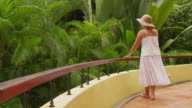 Woman walking on balcony overlooking tropical jungle. video