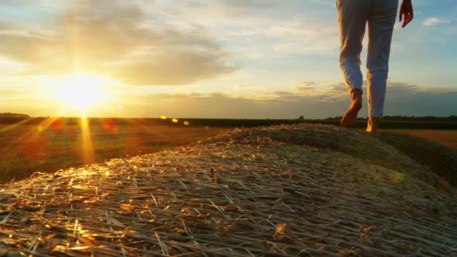 HD: Woman Walking On Hay Bales At Sunset video