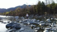 Woman walking on rocks by the river video