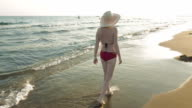 A woman walking on the beach at the sunset dawn video
