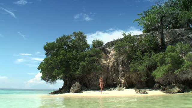 Woman walking on the beach of a desert tropical island video