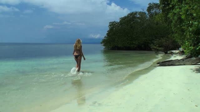 Woman walking on the lagoon along a desert tropical island video
