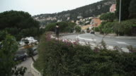 Woman walking on the road at the mediterranean city along green bushes and flowers video