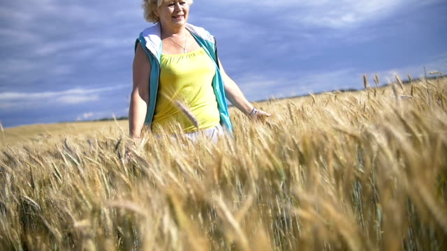 Woman walking on wheat field and smiling, Golden field against a blue sky video