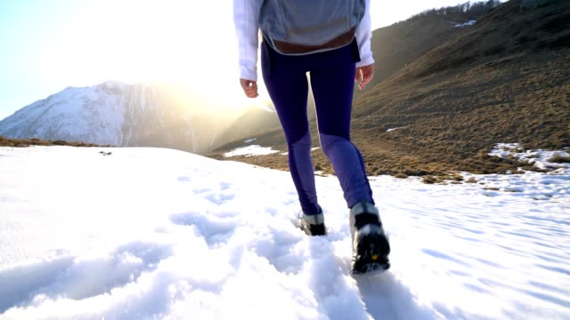 Woman walking on winter mountain trail at sunset video