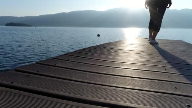 Woman walking on wooden jetty by the lake video