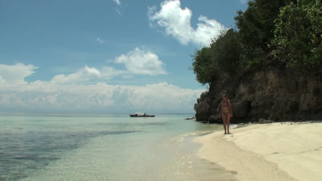 Woman walking onshore; a canoe is crossing the lagoon video