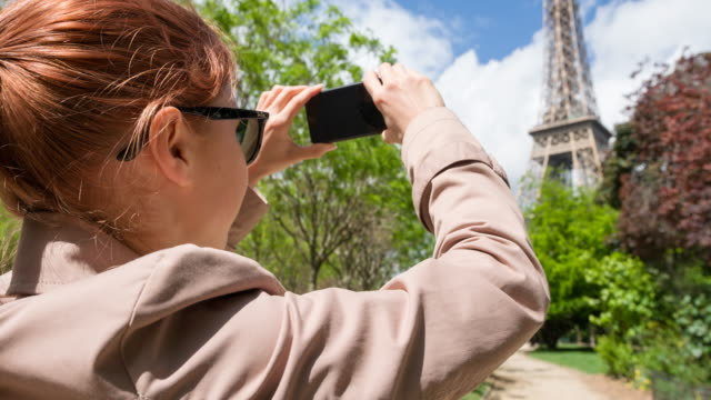 Woman walking the streets of Paris and taking pictures of Eiffel Tower video