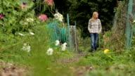 Woman walking through a community garden video