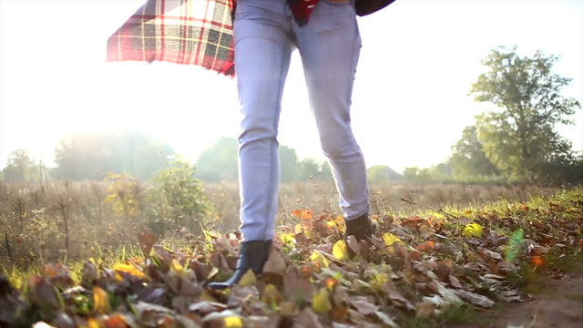 Woman walking through autumn leaves on ground video