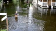 Woman Walking through Flooded Neighborhood HD video