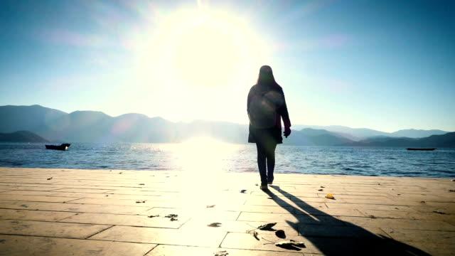 woman walking to lake on wooden pier video