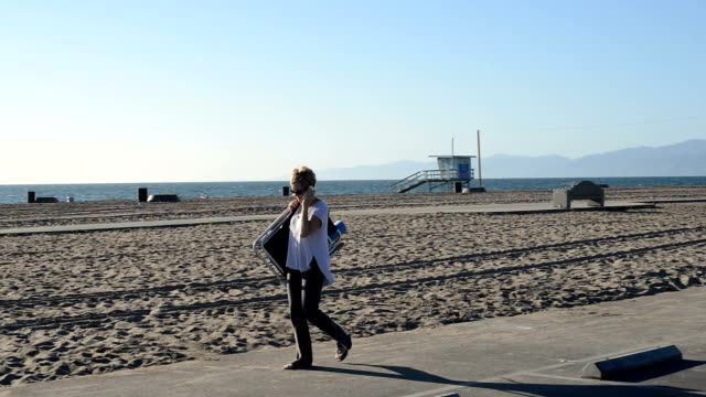 Woman Walking to the Beach and Talking on Phone video