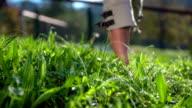 Woman walking trough the wet grass barefoot video
