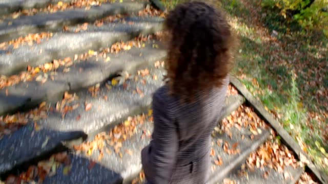 Woman walking up on ladder steps with autumn leaves video