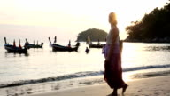 Woman walks along beach, looks out to boats in shallows video