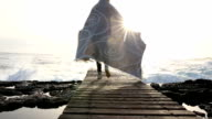 Woman walks along boardwalk above sea, wrapped in blanket video