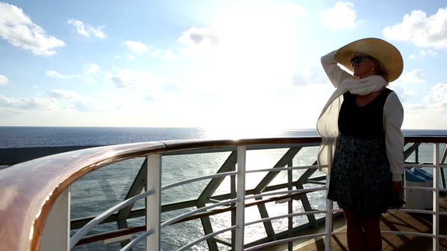 Woman walks along deck railing, above Mediterranean Sea video