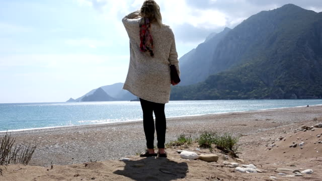 Woman walks along deserted beach, with digital tablet video