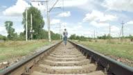 Woman walks along railway tracks in countryside video