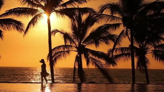 Woman walks by pool at tropical resort, sunset video