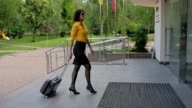 A woman walks into a hotel with a suitcase. video