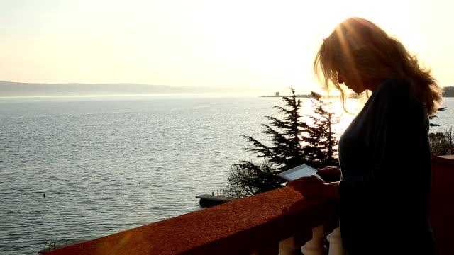 Woman walks onto terrace with digital tablet, sunrise video
