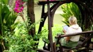 Woman walks to bench, uses digital tablet, tropical riverside video