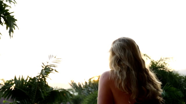 Woman walks to jungle overview, looks off video