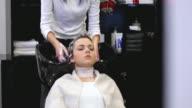 Woman washing hair in salon video