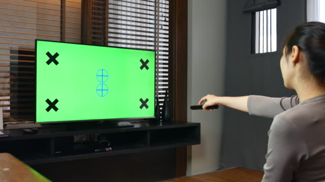 Woman Watching chroma key TV and changing channel at home video