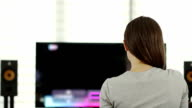 Woman watching the TV in the living room, time lapse video