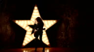 woman wearing leather jacket and playing a guitar, shining star in the background, slow motion, silhouette video