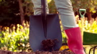 Woman wearing pink rubber boots using shovel video