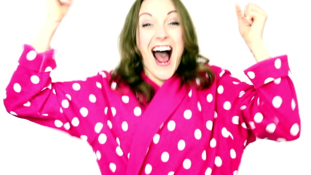 Woman wearing pink spotted bathrobe dressing gown cheering and celebrating. video