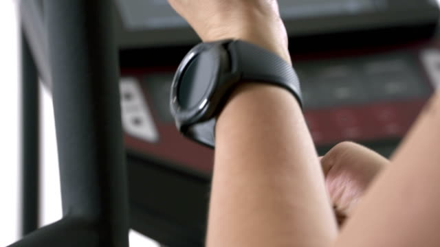 Woman wearing smart watch preparing for cardio exercise on elliptical trainer video