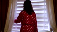 Woman wearing spotted bathrobe dressing gown opening window blind. video