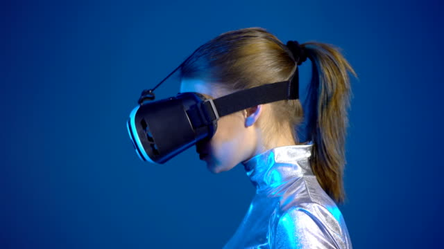 Woman wearing virtual reality googles looking at blank copy space video