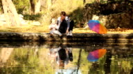 woman with a baby playing in the pond video