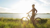 Woman with a bicycle looking at view. video