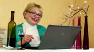 Woman with a bottle of wine sits at a table and communicates via laptop video