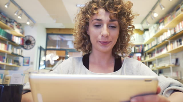 Woman with a digital tablet in the bookstore. video
