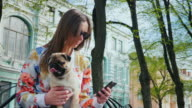 A woman with a dog is sitting on a bench in the park. Uses a mobile phone video