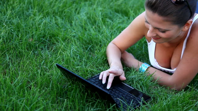 Woman with a laptop on the grass in the park video