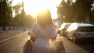 Woman with a shopping bags at sunset video