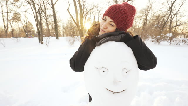 Woman with a snowman looking at camera. video